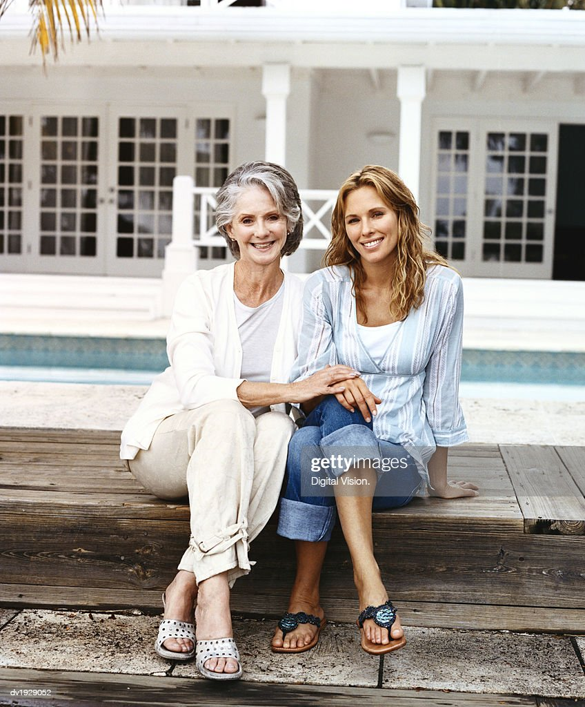 Portrait of a Senior Woman and Her Mature Daughter Sitting on Poolside Decking : Stock Photo