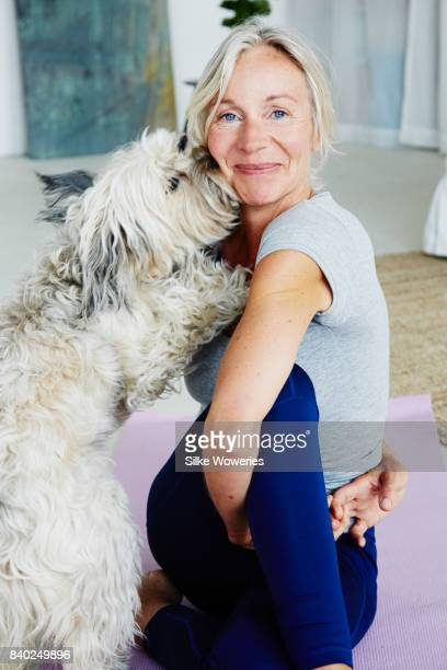 portrait of a senior woman being distracted by her dog while doing yoga at home