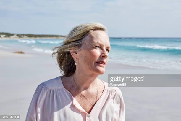 portrait of a senior woman by the sea - frau 65 jahre stock-fotos und bilder