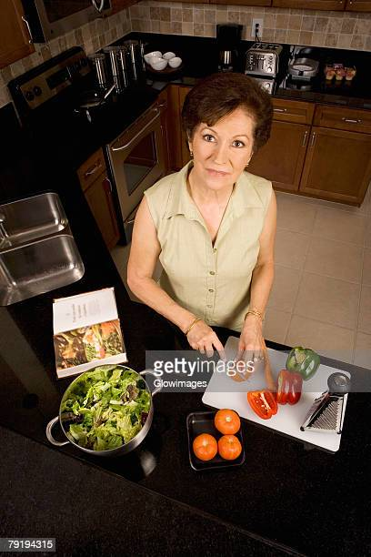 Portrait of a senior woman cutting vegetables on a cutting board in the kitchen