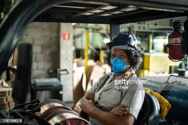 portrait of a senior woman driving a forklift in an industry - essential services stock pictures, royalty-free photos & images