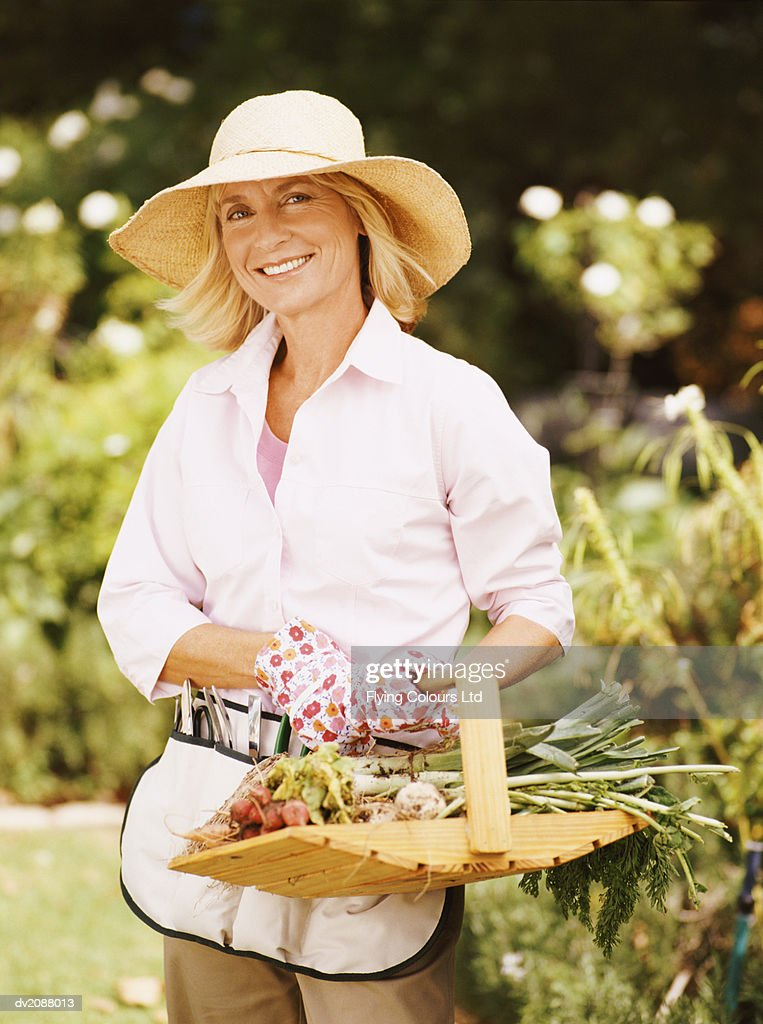 Portrait of a Senior Woman Holding a Basket of Vegetables : Stock Photo