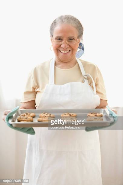 Portrait of a senior woman holding cookies in a plate