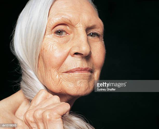 Portrait of a Senior Woman Holding Her Long, Grey Hair