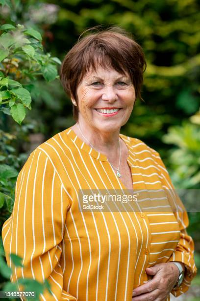 portrait of a senior woman in her garden - morpeth stock pictures, royalty-free photos & images