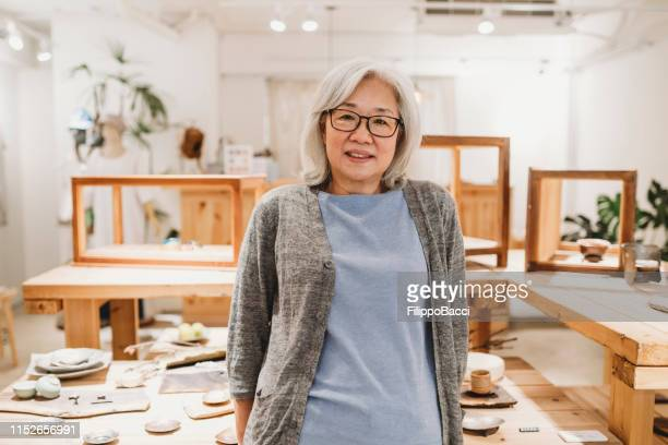portrait of a senior woman inside her store - white hair stock pictures, royalty-free photos & images