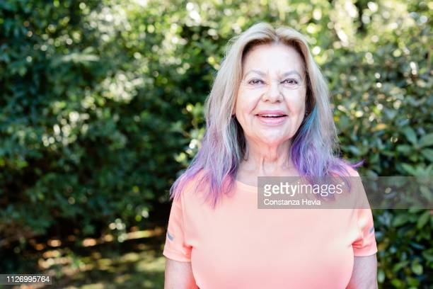 portrait of a senior woman laughing looking at the camera - purple hair stock pictures, royalty-free photos & images