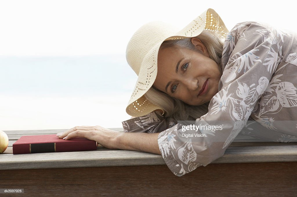 Portrait of a Senior Woman Lying on Wooden Decking by the Sea With a Book : Stock Photo