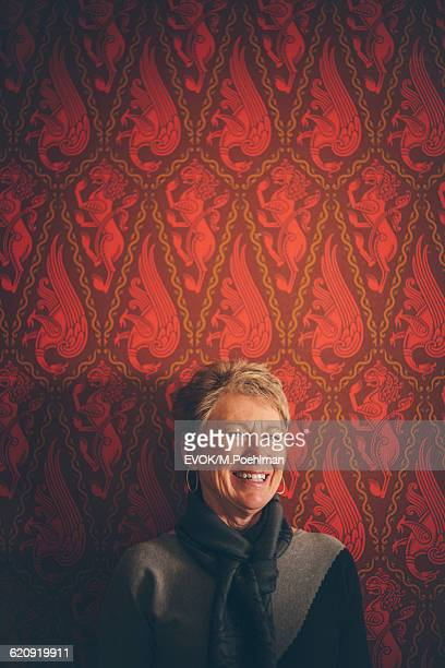 Portrait of a Senior Woman on red wallpaper