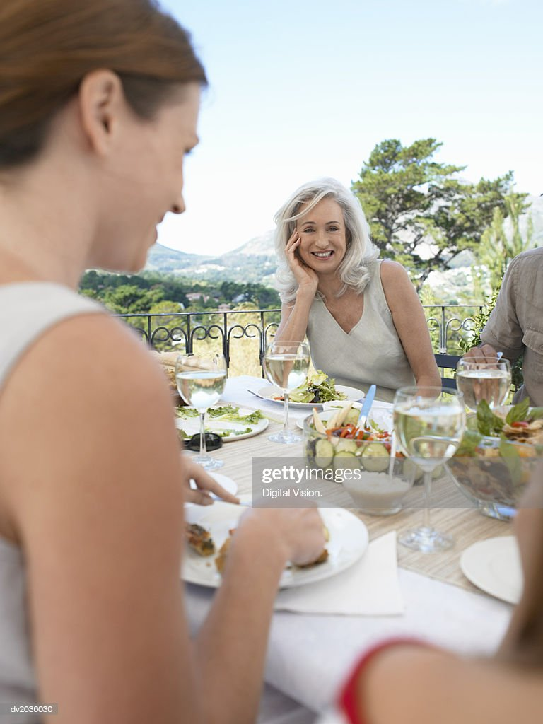 Portrait of a Senior Woman Sitting at a Table Outdoors Having a Meal : Stock Photo