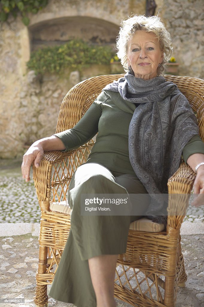 Portrait of a Senior Woman Sitting in a Wicker Armchair on a Terrace : Stock Photo