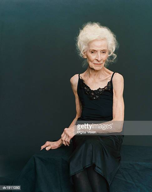 portrait of a senior woman sitting in an evening gown against a black background - evening gown stock photos and pictures