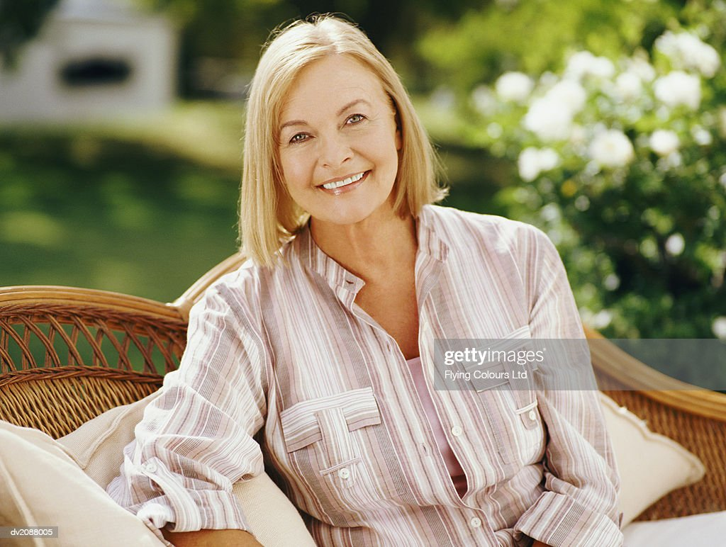 Portrait of a Senior Woman Sitting on a Wicker Seat in a Domestic Garden : Stock Photo