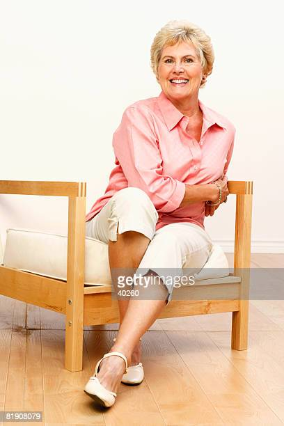 portrait of a senior woman smiling and sitting on a chair - pedal pushers stock pictures, royalty-free photos & images