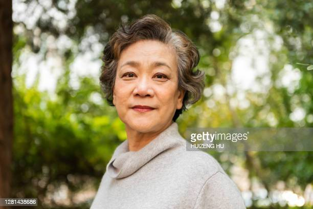 portrait of a senior woman smiling outdoor. happy senior woman standings outdoor - confidence stock pictures, royalty-free photos & images