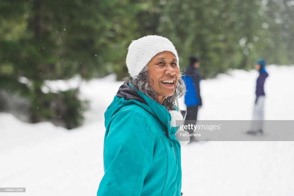 Portrait of a senior woman snowshoeing : Stock Photo