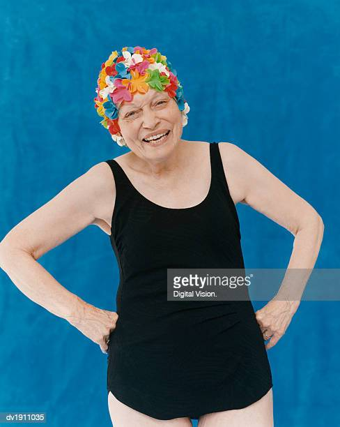 Portrait of a Senior Woman Standing in a Swimming Costume With Her Hands on Her Hips Wearing a Floral Swimming Cap