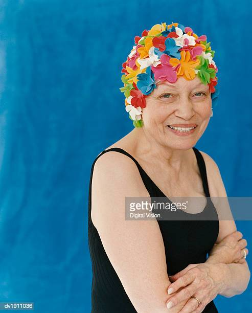 Portrait of a Senior Woman Standing in a Swimming Costume With Her Arms Crossed Wearing a Floral Swimming Cap