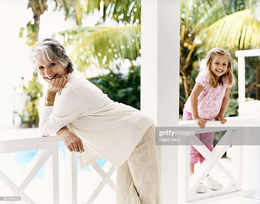 Portrait of a Senior Woman Standing on a Balcony With Her Young Granddaughter : Stock Photo