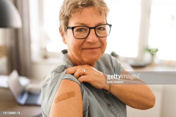 portrait of a senior woman that is vaccinated - long sleeved stock pictures, royalty-free photos & images