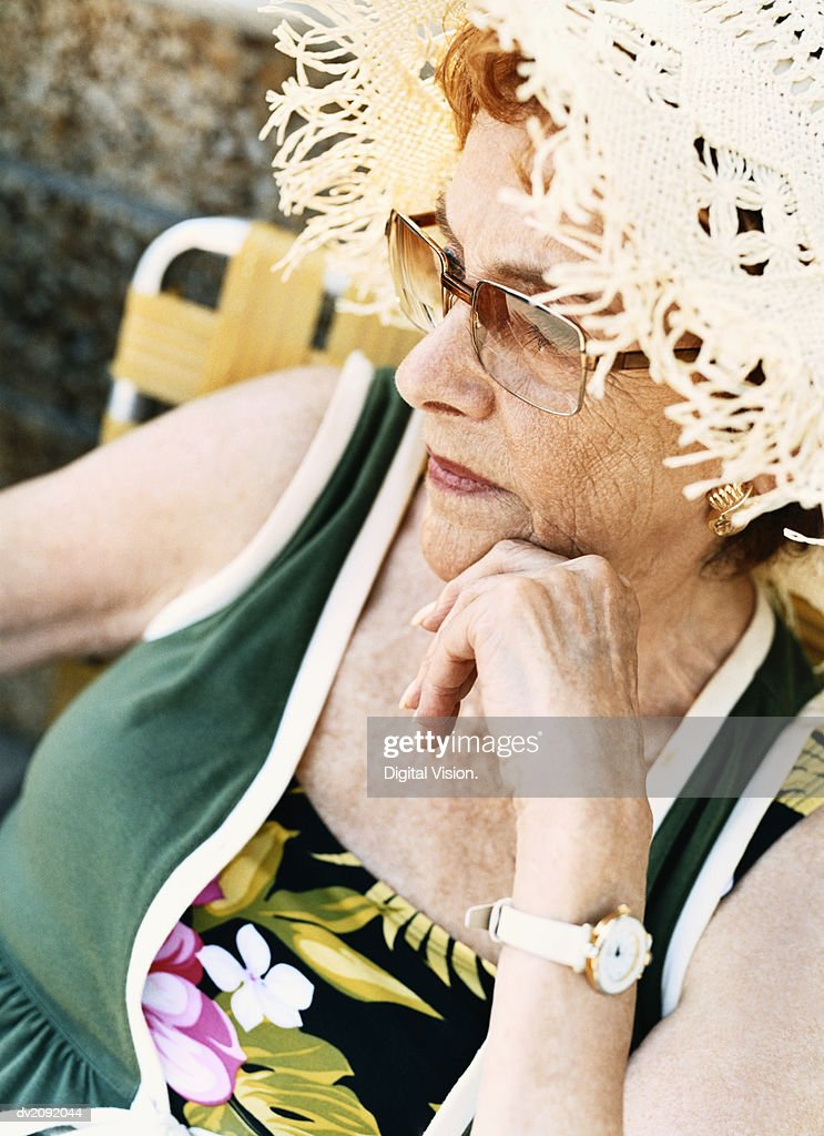 Portrait of a Senior Woman Wearing a Straw hat and Sunglasses : Stock Photo