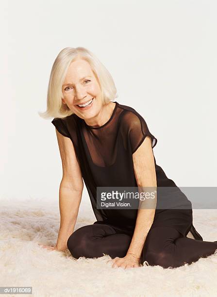 portrait of a senior woman wearing black clothes, kneeling on a white rug - old women in pantyhose stock pictures, royalty-free photos & images