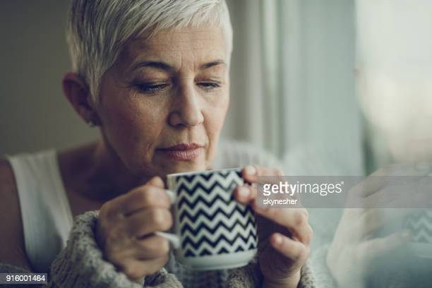 portrait of a senior woman with coffee cup by the window. - sensory perception stock pictures, royalty-free photos & images
