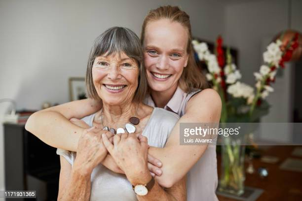 portrait of a senior woman with daughter at home - tochter stock-fotos und bilder