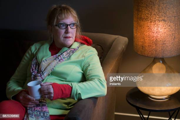 Portrait of a serious 58 year old woman, sitting and relaxing with a cup of tea in her hands.