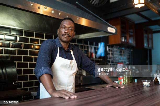 portrait of a serious barista standing behind the counter - owner stock pictures, royalty-free photos & images