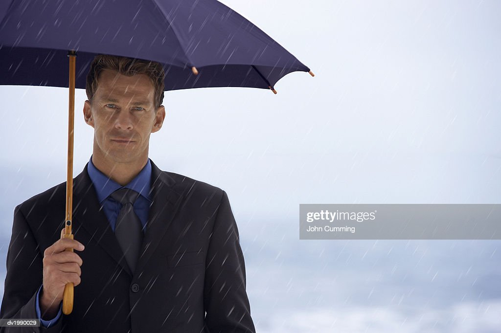 Portrait of a Serious Businessman Sheltering Underneath an Umbrella in the Rain : Stock Photo