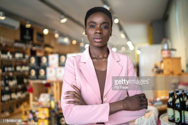 portrait of a serious businesswoman/ business owner standing with arms crossed in a market - authority stock pictures, royalty-free photos & images