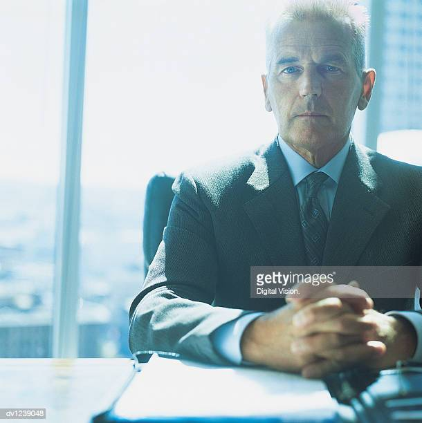 Portrait of a Serious CEO Sitting at His Desk With His Hands Together