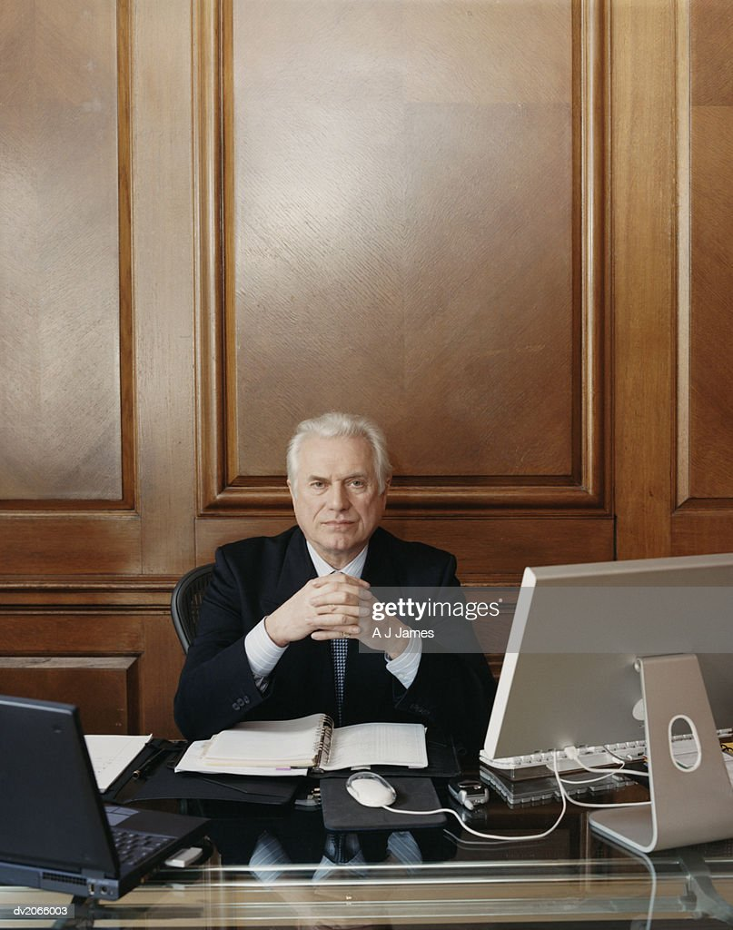Portrait of a Serious Looking CEO Sitting at His Desk : Stock Photo