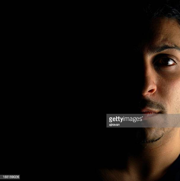 portrait of a serious man with half his face in the shadows - iranian culture stock photos and pictures