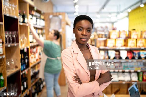 portrait of a serious owner / businesswoman standig with arms crossed in a store - bar drink establishment stock pictures, royalty-free photos & images