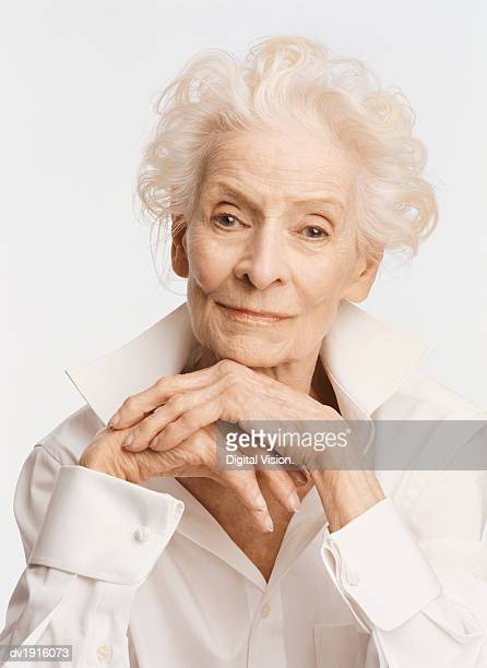 Portrait of a Serious Senior Woman Wearing a White Shirt and Resting Her Chin on Her Hands