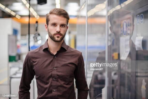 portrait of a serious young businessman in a factory - só homens jovens imagens e fotografias de stock