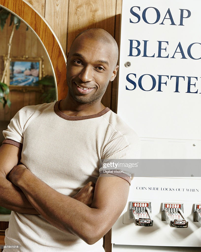 Portrait of a Shaven Head Man Leaning Against a Coin Operated Machine in a Launderette : Stock Photo