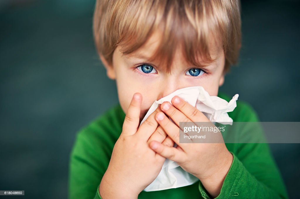 Portrait of a sick boy cleaning his nose : Foto de stock