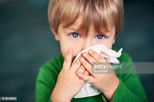 portrait of a sick boy cleaning his nose - krankheit stock-fotos und bilder