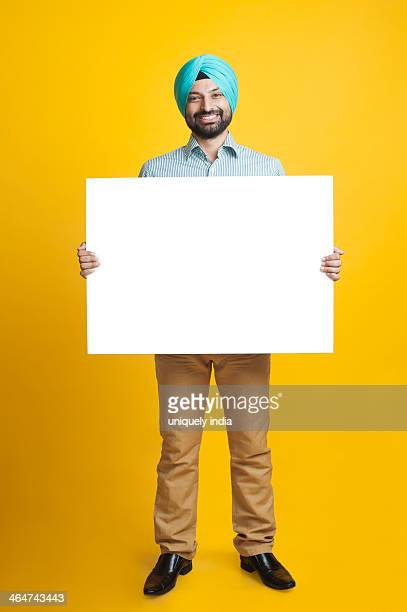 Portrait of a Sikh man holding a blank placard and smiling