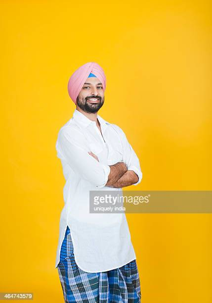 Portrait of a Sikh man standing with his arms crossed and smiling