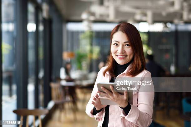 portrait of a singaporean business woman using a tablet - シンガポール文化 ストックフォトと画像