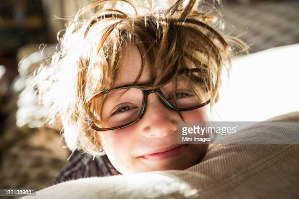 portrait of a six year old boy with disheveled hair and oversized glasses waking up.  bedhead hair. - crazy hair stock pictures, royalty-free photos & images
