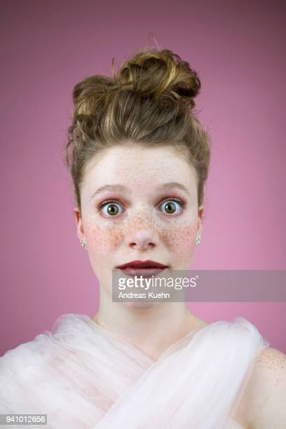 Portrait of a sixteen year old teenage girl with an updo, pale skin, freckles and big eyes in front of a purple colored background.