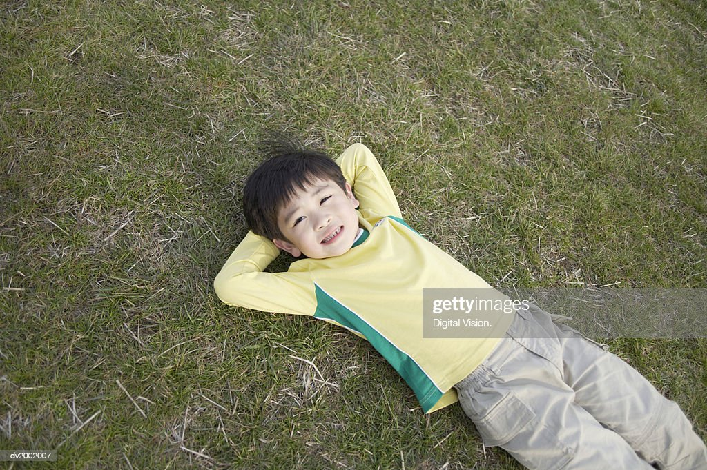Portrait of a Small Boy Lying on Grass : Stock Photo