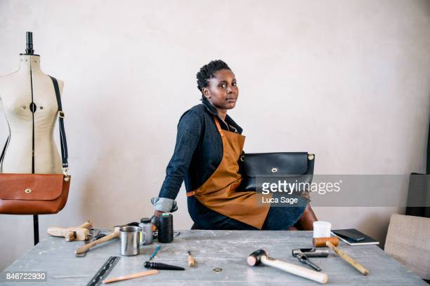 portrait of a small business owner sitting behind her desk, with finished handbag - black purse stock pictures, royalty-free photos & images