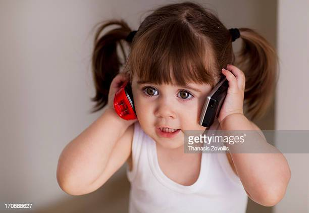 Portrait of a small girl talking on phone