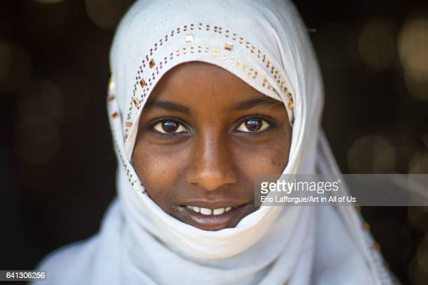 Portrait of a smiling Afar tribe girl with a white veil on January 15 2017 in Afambo Ethiopia